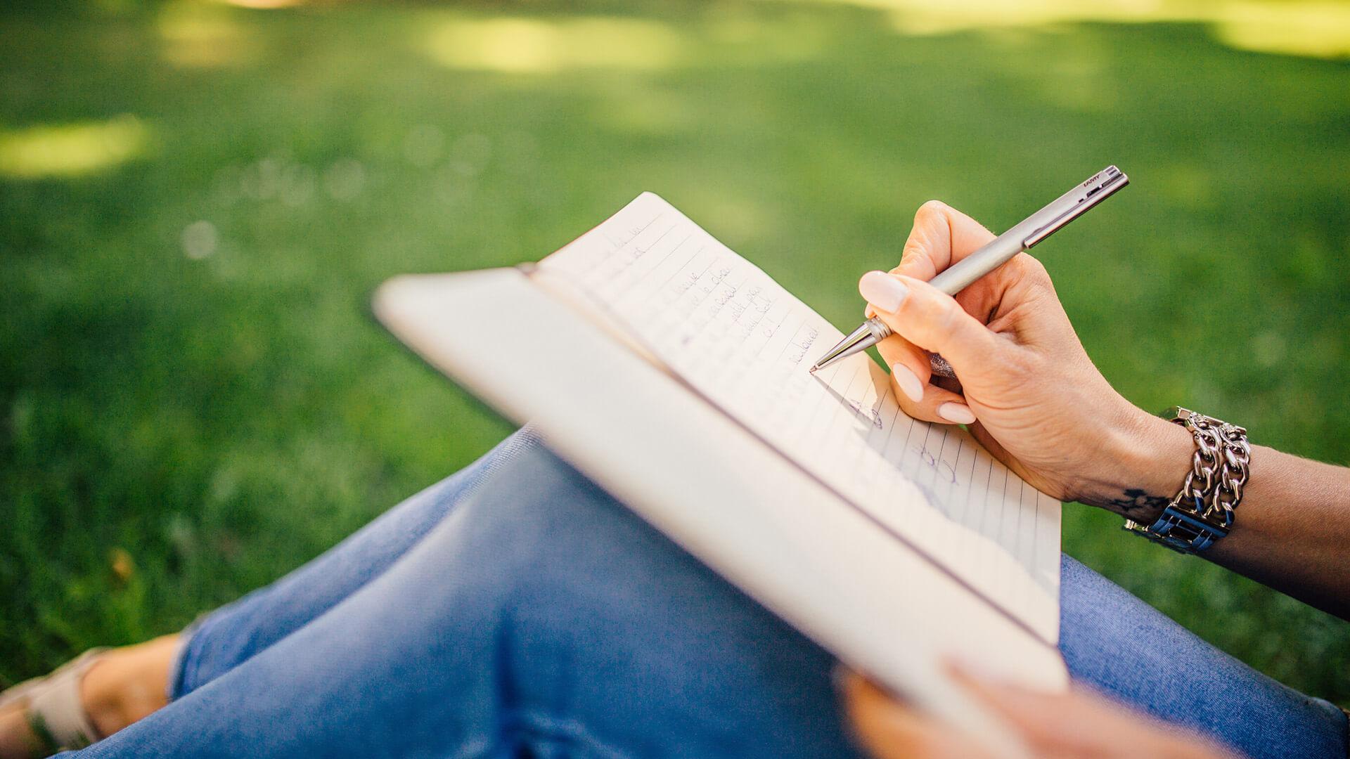 Nuori nainen kirjoittaa puistossa